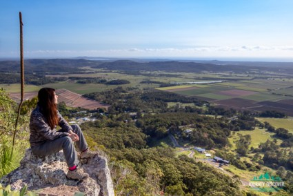 North east views from Mt Ninderry, Sunshine Coast, Queensland, Australia  Woman sitting on rocky outcrop overlooking a vast plain