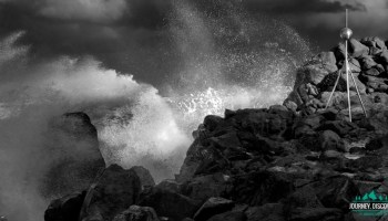 B&W Big waves crash over cobbled rocks