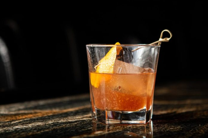 A picture of a orange cocktail sitting on a glossed wood bar at the Haberdasher Cocktail Bar in San Jose