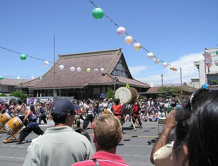 A traditional Japanese building stands in the background of a street scene in Japan Town, San Jose during Obon Festival