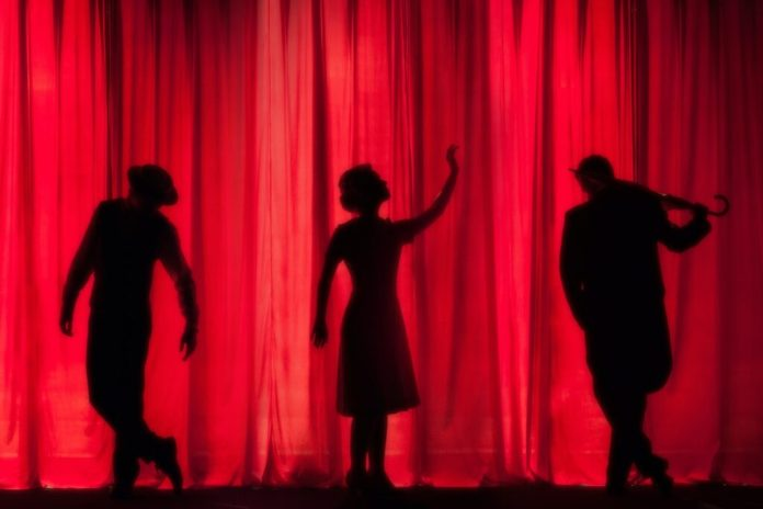 Three silhouettes of actors on a stage standing in front of a red curtain at the Tabard theater in San Jose