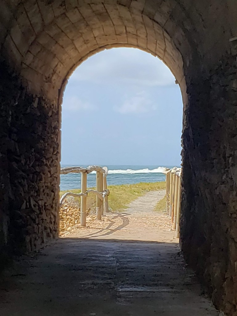 Distant ocean view seen through an arch