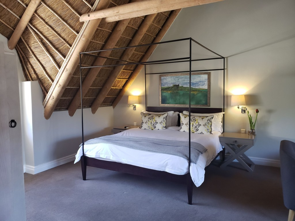 bed with poster frame under vaulted thatch ceiling