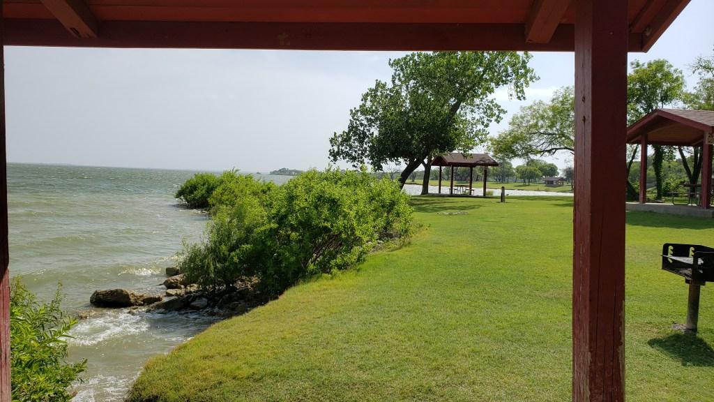 Green grass slopes alongside lake with pavilions
