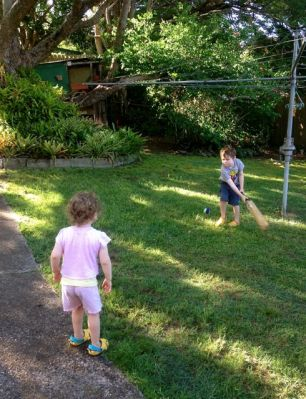 P and T playing backyard cricket.