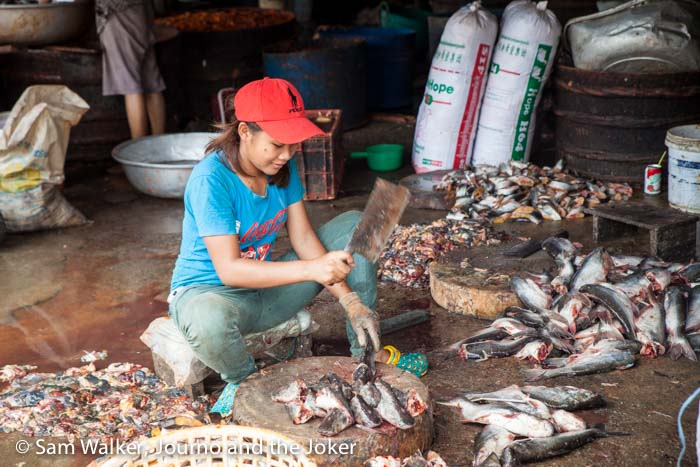 Woman chopping fish at the fish market