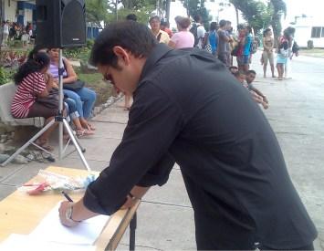 Firmando libro de condolencias en la Universidad de Oriente