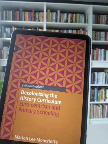 Cover of decolonising the history curriculum with a bookshelf in the background