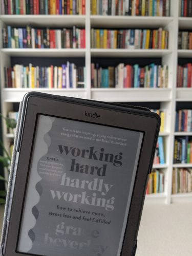 Cover of working hard, hardly working against a bookshelf