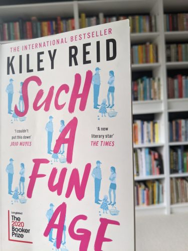 Such a fun age cover in front of a bookshelf