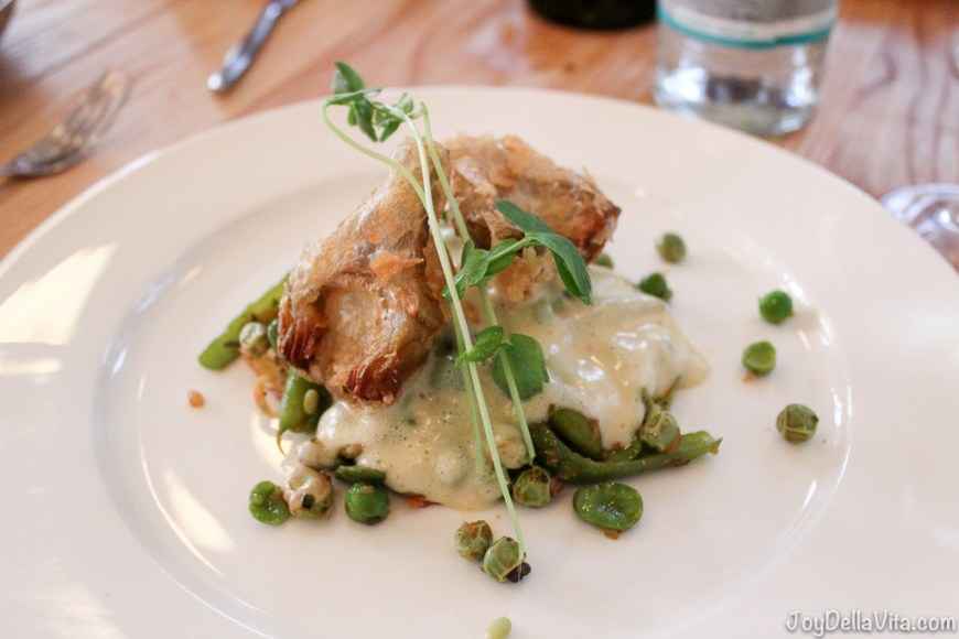 Fried artichokes with hollandaise sauce, beneath potato pancakes and peas / green beans