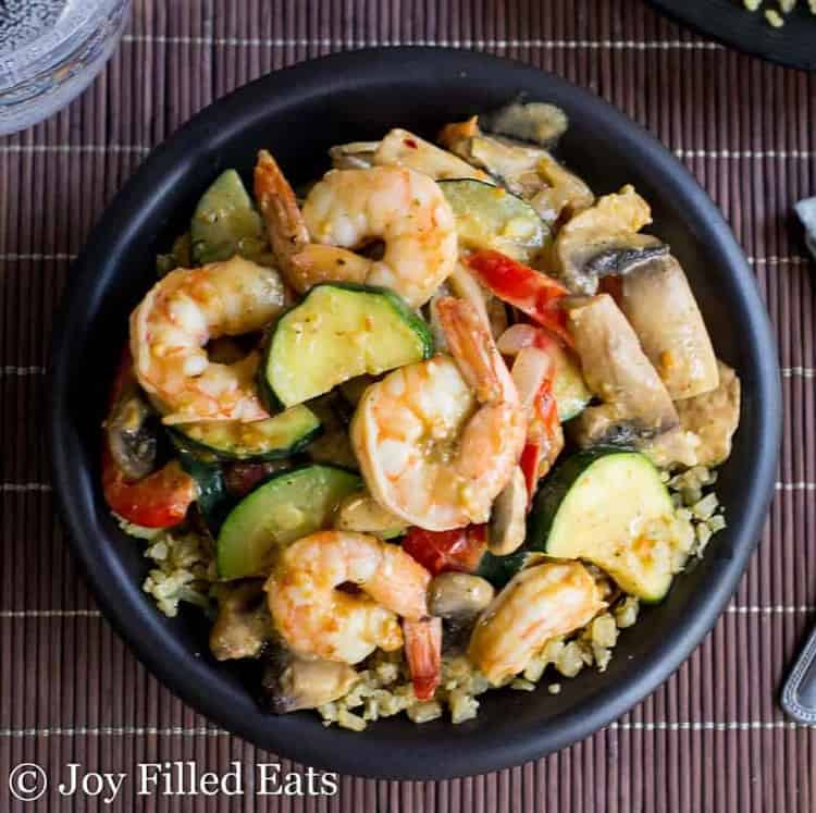 Cooked thai shrimp and vegetables in a black bowl on a bamboo placemat