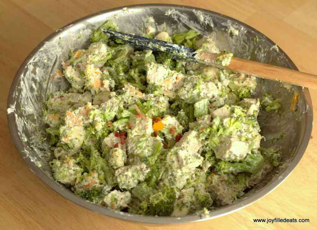 a large mixing bowl with cooked chicken and broccoli in a creamy sauce