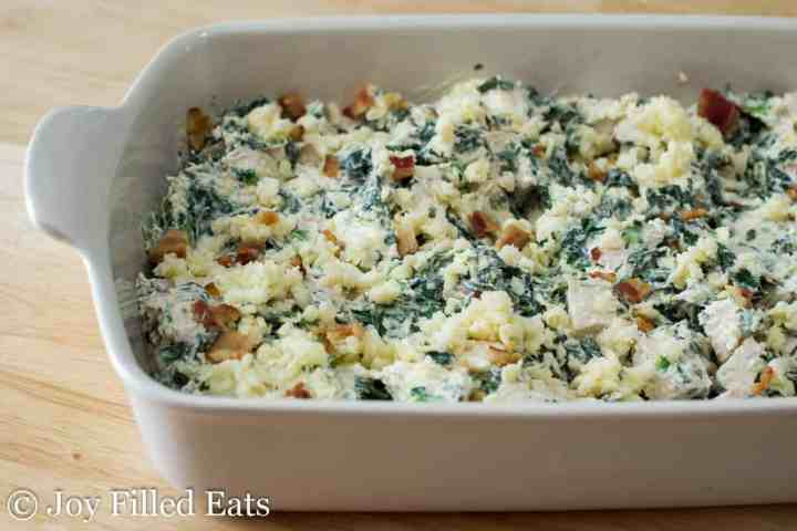 cooked chicken and spinach in a creamy sauce in a casserole dish topped with bacon and cheese Chicken Bacon Caesar Casserole