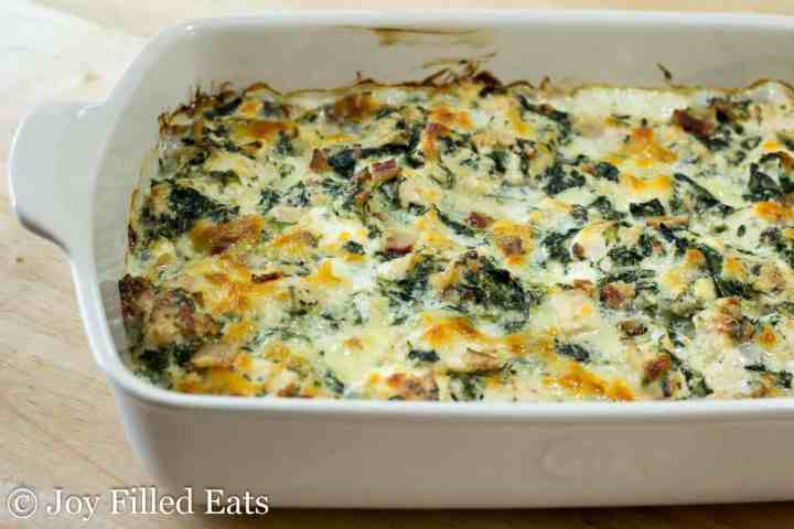 cooked chicken and spinach keto casserole in a creamy sauce in a large white casserole dish