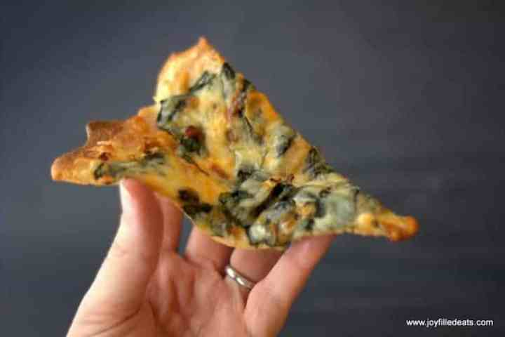 A hand holding a piece of keto pizza.