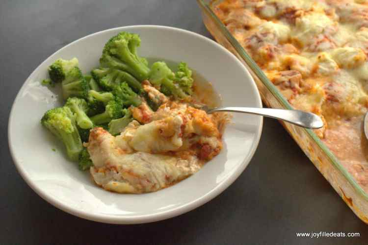 Pizza Chicken Casserole on a white plate with a side of broccoli.