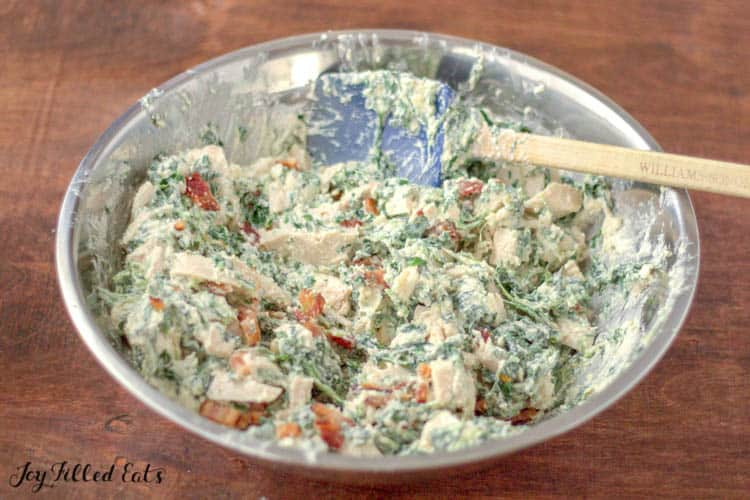 chicken spinach and bacon in a creamy sauce in a large bowl