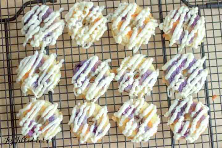 lemon blueberry donuts on a cooling rack with lines of cream cheese glaze on them