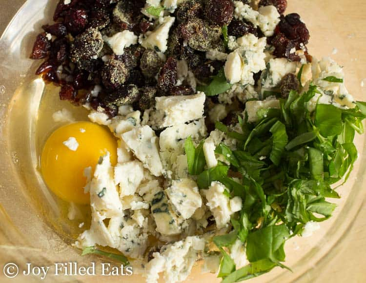 Bowl with basil, cheese, cranberries, egg, and seasonings for the baked turkey burgers