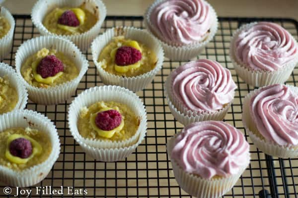 Cupcakes filled with lemon curd and a raspberry and topped with raspberry frosting