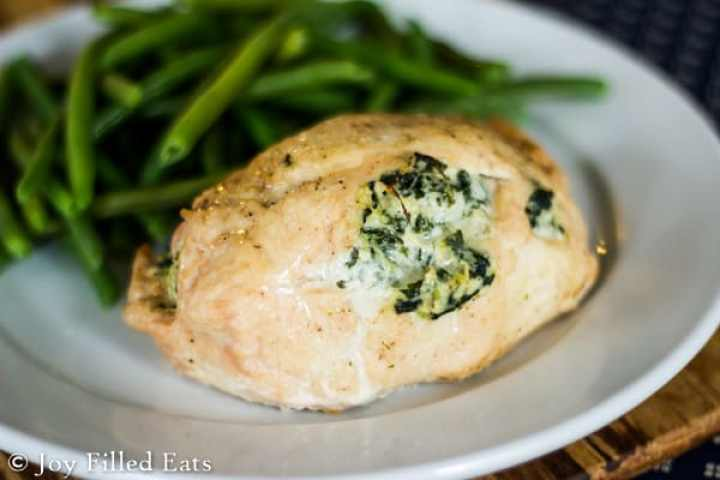 Spinach & Artichoke Stuffed Chicken Breasts on a white plate