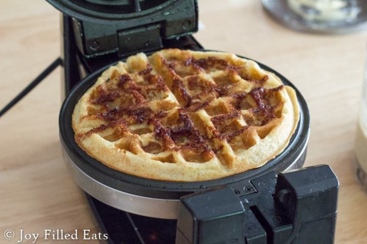 one of the Cinnamon Roll Waffles cooked and on the waffle maker
