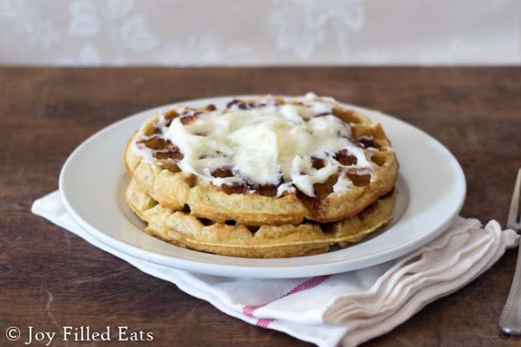two Cinnamon Roll Waffles with Cream Cheese Icing stacked on a white plate