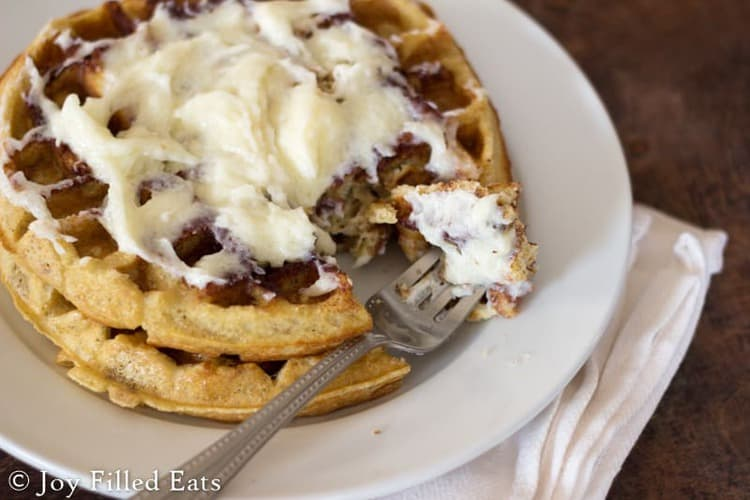 two Cinnamon Roll Waffles with Cream Cheese Icing on a white plate with a fork