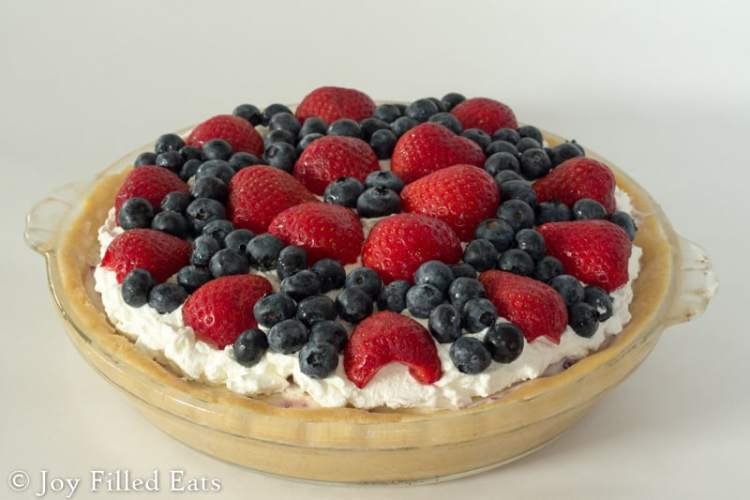 an ice cream pie topped with strawberries and blueberries