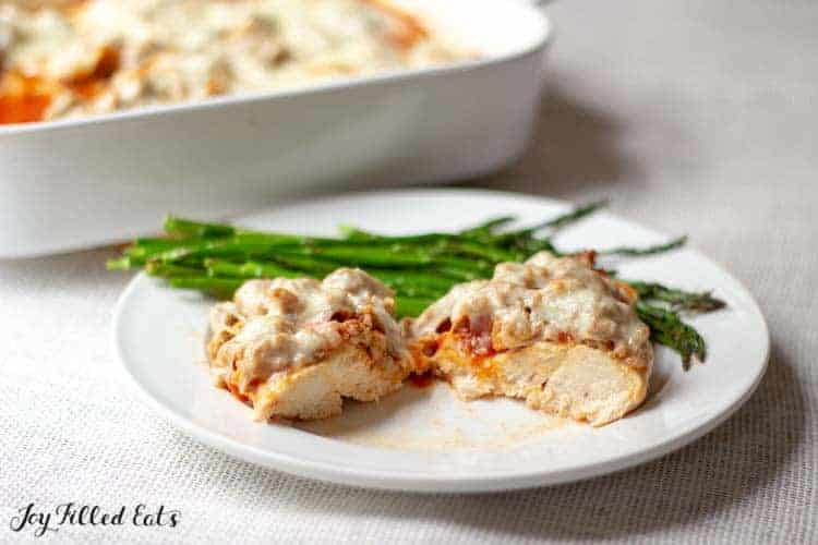 Italian Baked Chicken with Sausage on a white plate with asparagus