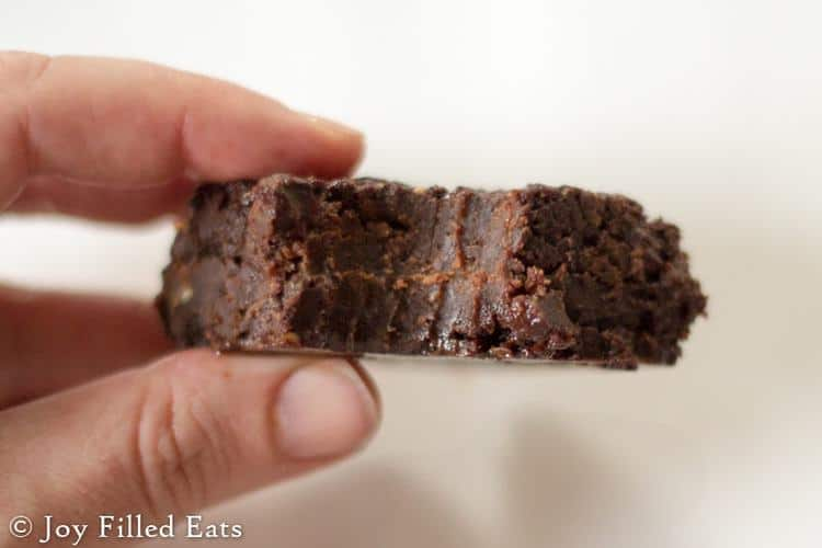 a hand holding a fudgy brownie with coconut oil with a bite out of it