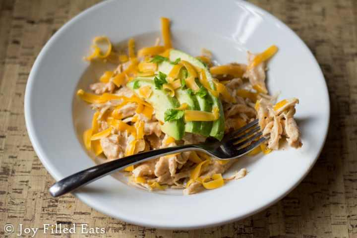 Shredded salsa chicken recipe in a white bowl with a fork on a cork placemat. Topped with avocado, cheddar, and cilantro.