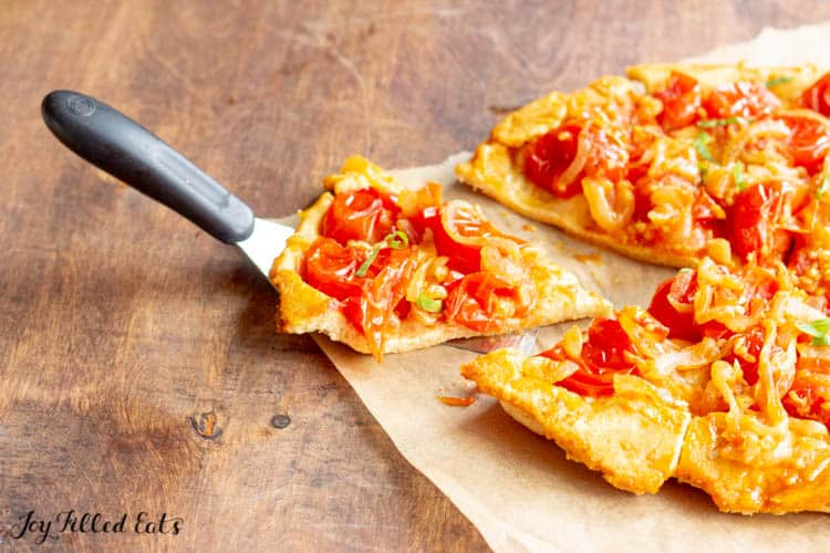 a piece of the tomato tart on parchment paper with a metal spatula