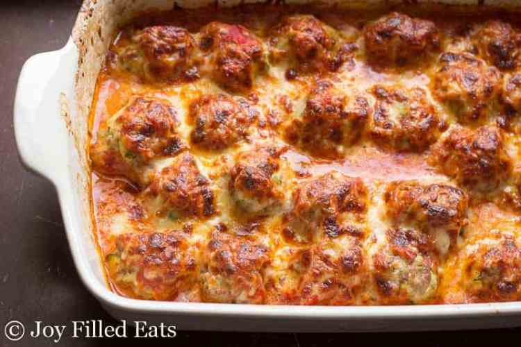 a white casserole dish with a baked meatball casserole