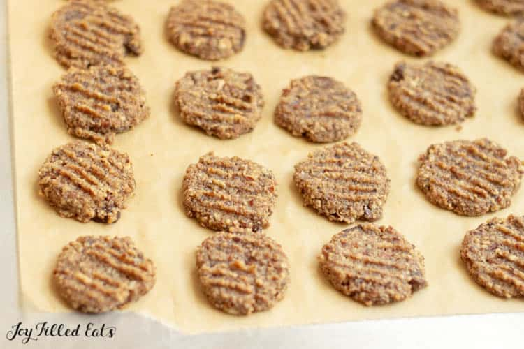 cookie tray lined with parchment paper with pecan cookies