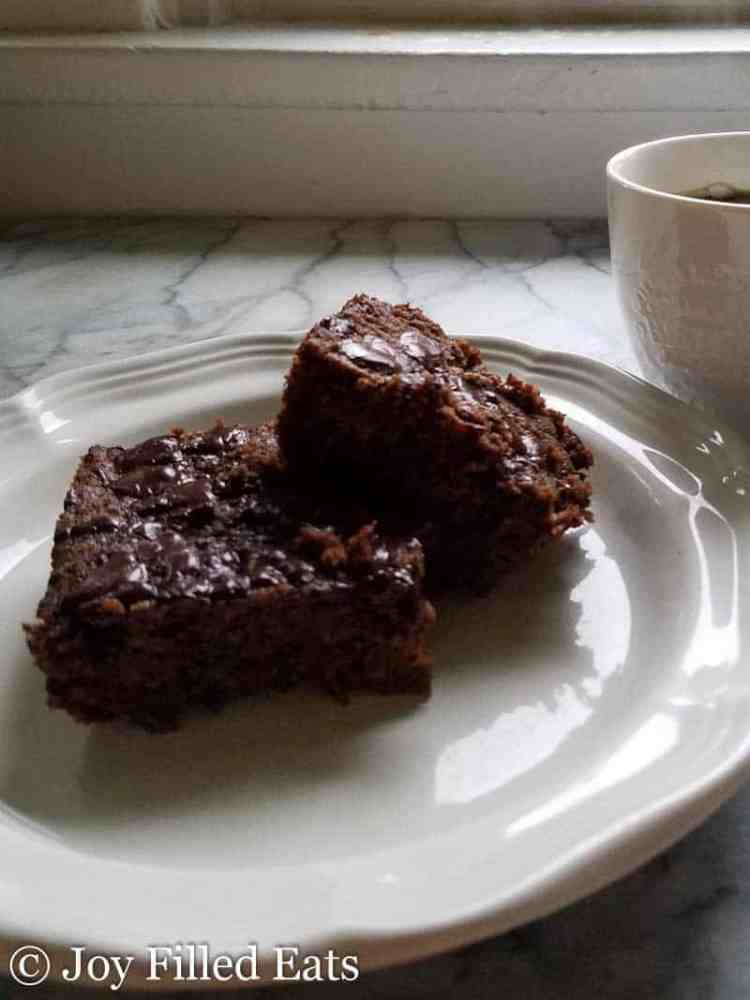 Brownies stacked on a white plate on a white and gray marble counter with a mug of coffee in the background