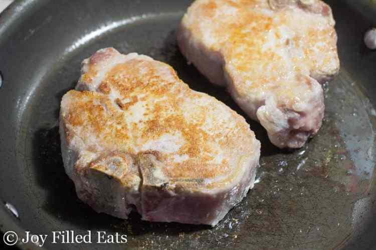 pork chops being browned in a frying pan