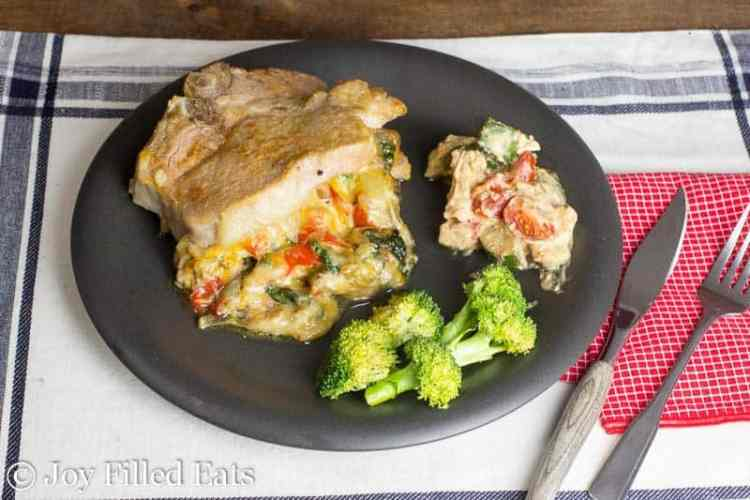 Cheesy Spinach Stuffed Pork Chops with Peppers & Onions on a black plate with a side of broccoli and creamy zucchini.