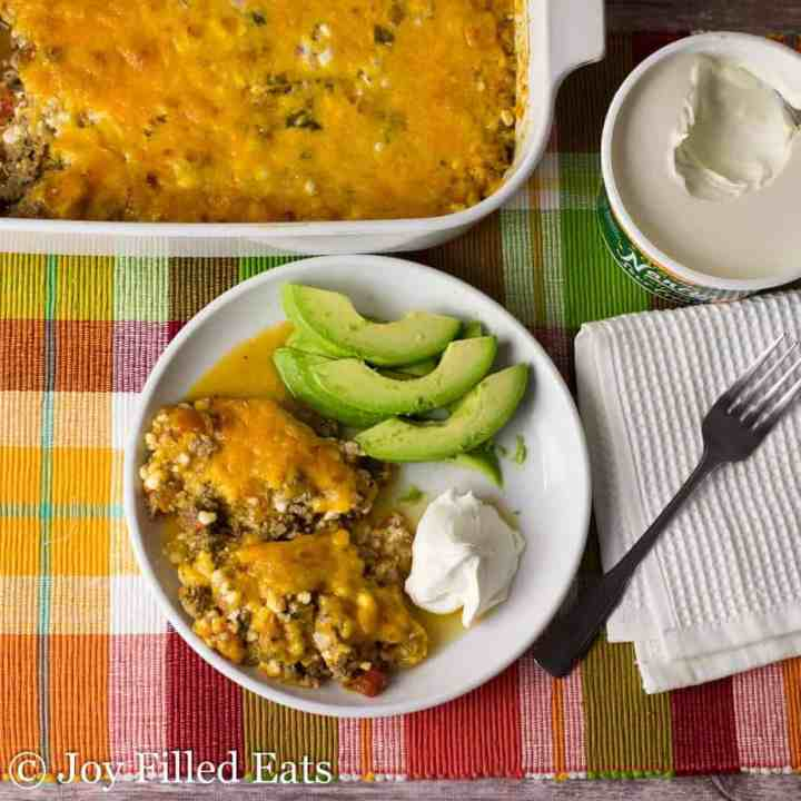 Overhead view of the Easy Taco Casserole Recipe served on a white plate with sour cream and avocado