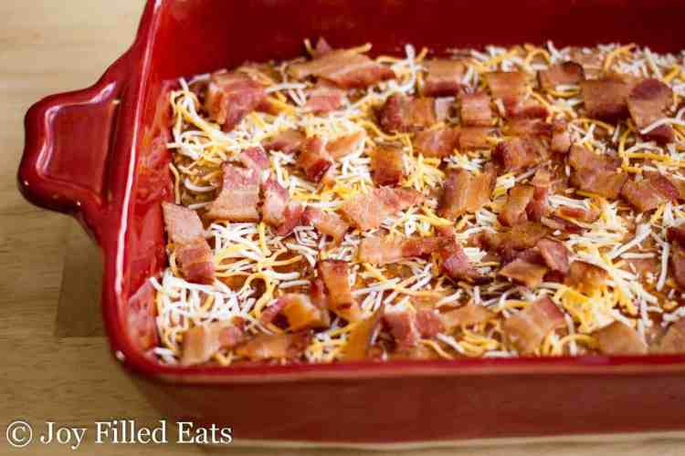 Uncooked meatloaf topped with shredded cheese and bacon in a red casserole dish