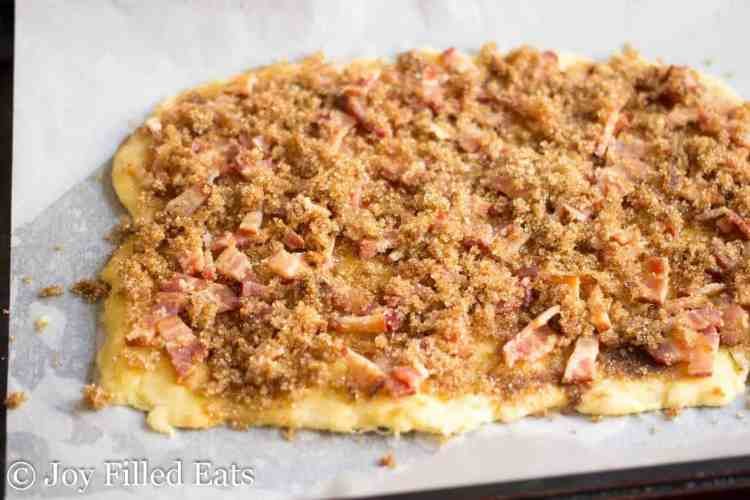 raw dough with cooked bacon and brown sugar on top