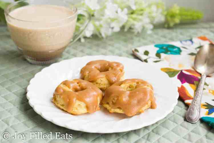 Three Mini Brown Butter Caramel Donuts on a white plate with flowers and a cup of coffee behind