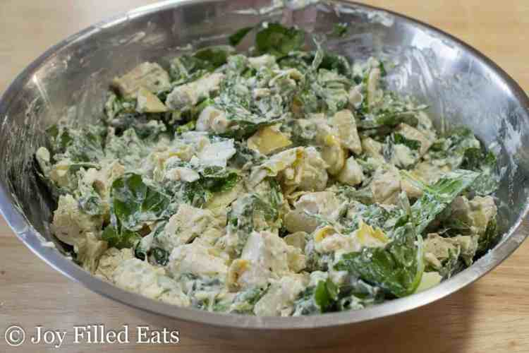 The ingredients for the Spinach & Artichoke Chicken Casserole mixed together in a large bowl.