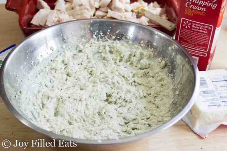 A large stainless bowl with the creamy sauce for the Easy Mozzarella & Pesto Chicken Casserole.
