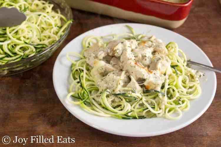Easy Mozzarella & Pesto Chicken Casserole on a white plate on top of zucchini noodles.