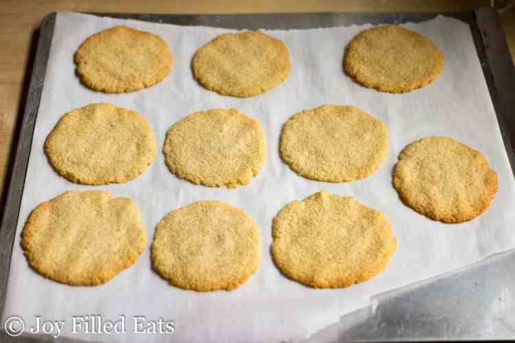 Golden round baked cookies on a parchment lined baking sheet