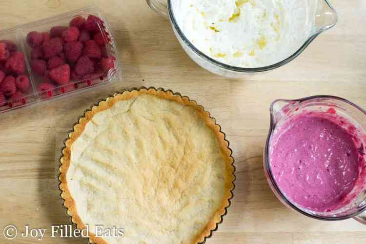 a baked tart crust, fresh raspberries, whipped cream, and raspberry puree in bowls