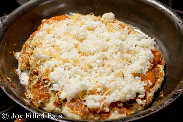 Cheese on top of the cooked dough in a skillet