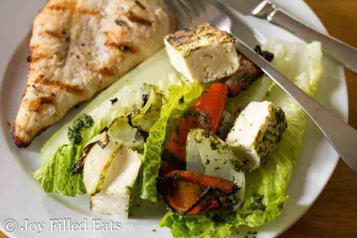 A side of salad next to a grilled chicken breast